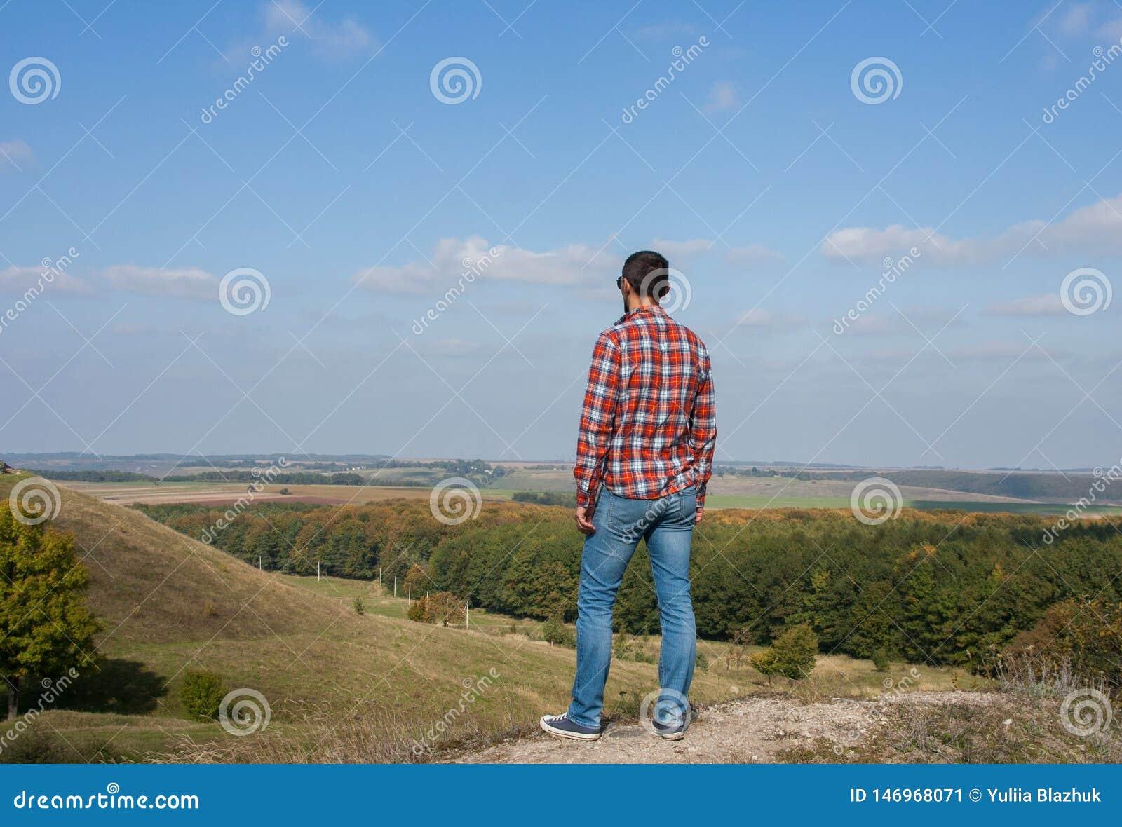 Position de jeune homme sur une colline appréciant le paysage Concept de voyage et de libert?