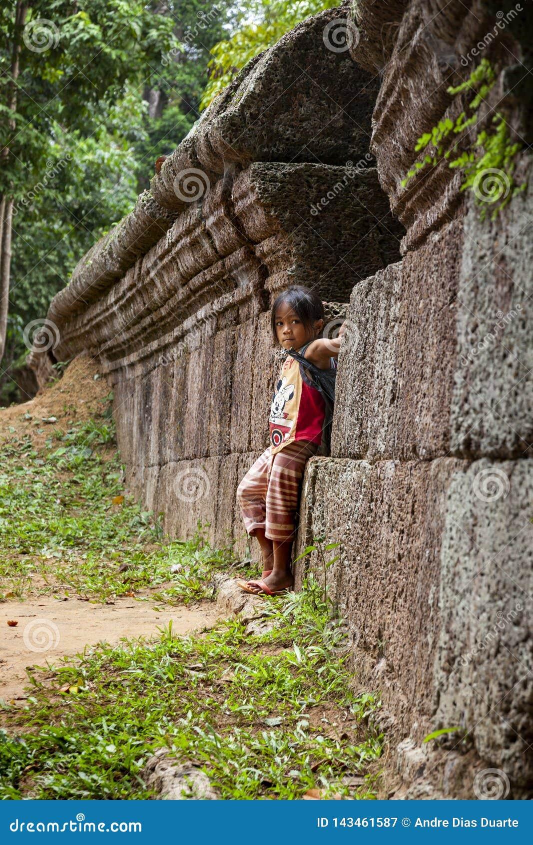 Position de petite fille contre un vieux mur en pierre