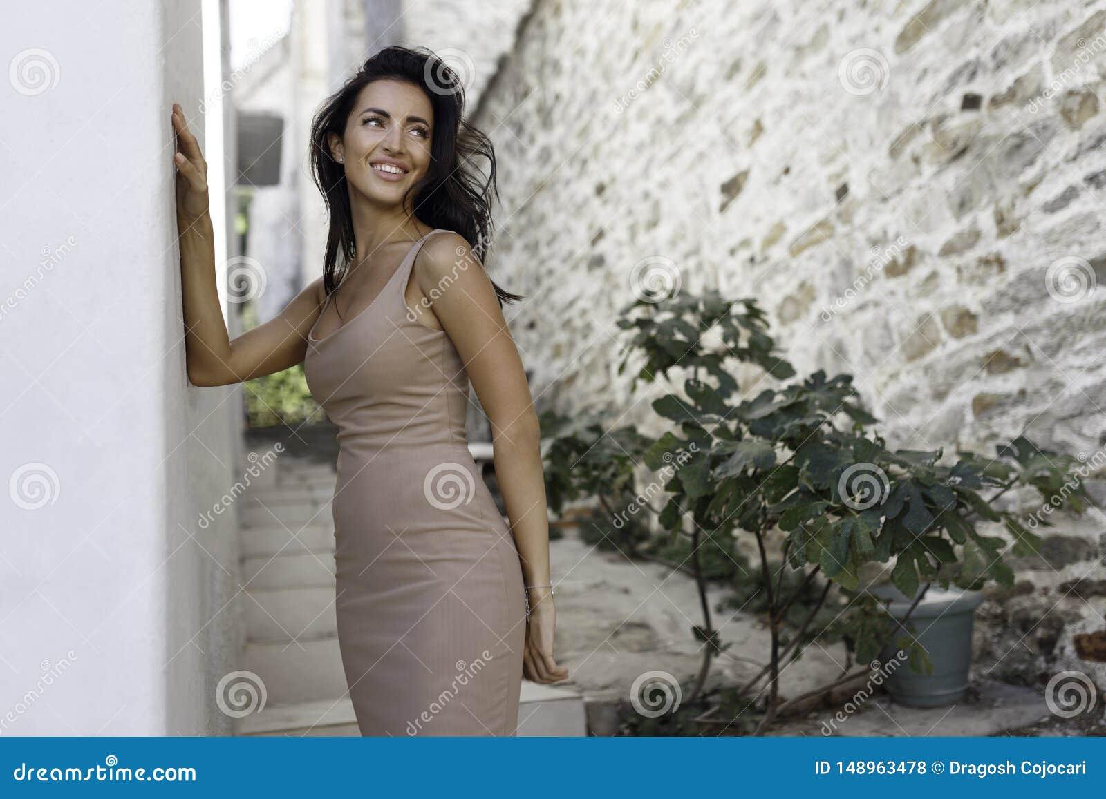 Position de sourire de fille pr?s du vieux mur en pierre Belle femme avec de longs cheveux posant l ext?rieur sexy dans les vacan
