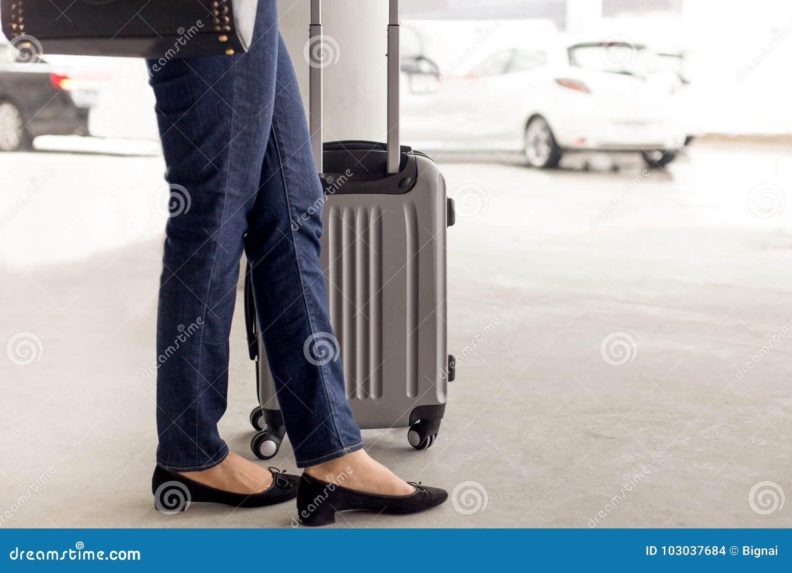 Position de touristes de femme avec le taxi de attente de bagage