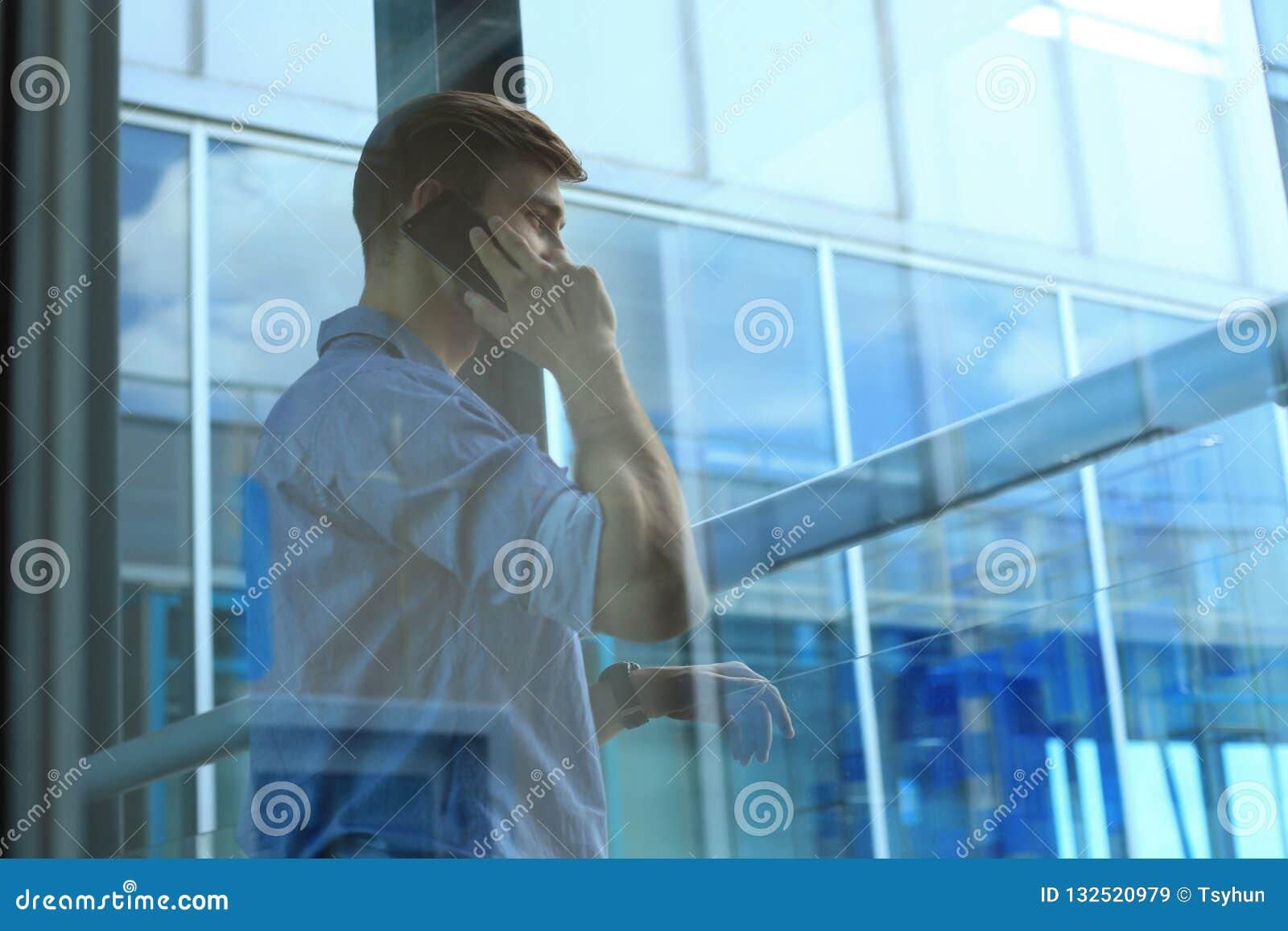 Position et à l aide de sourire d homme d affaires du téléphone portable dans le bureau
