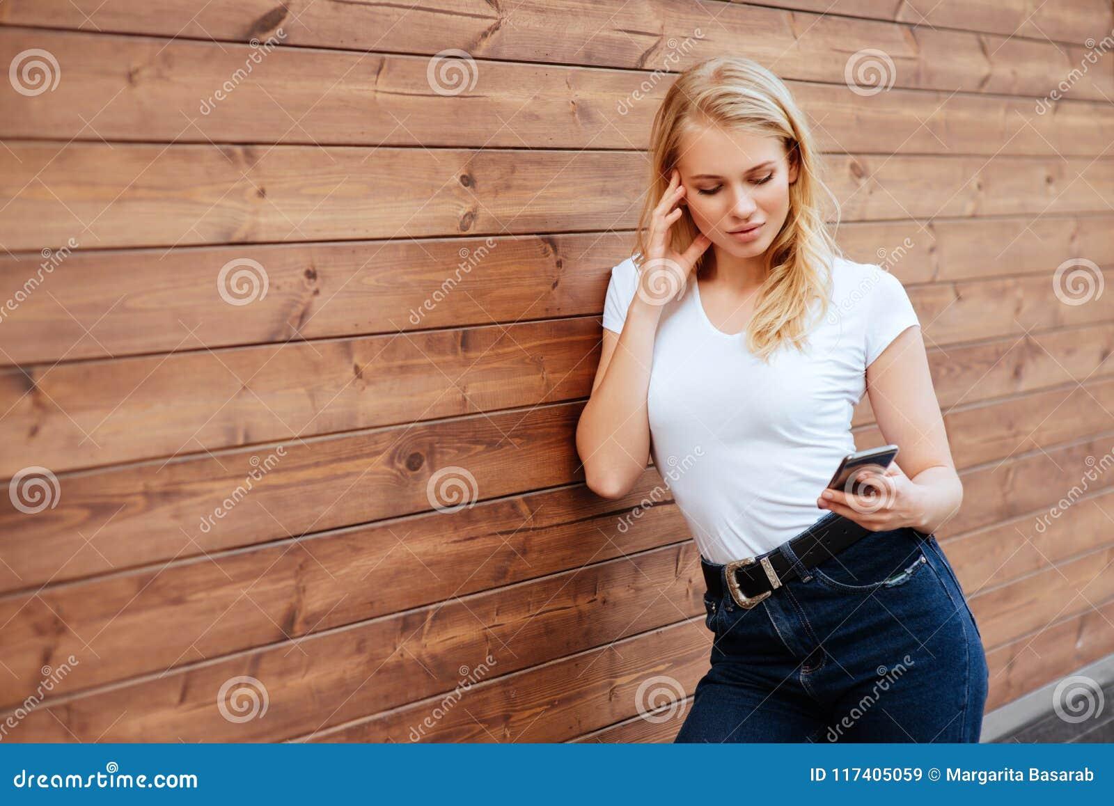 Position femelle riante attrayante avec le téléphone portable sur le fond en bois de mur