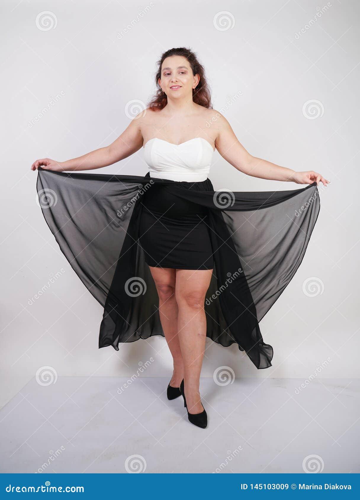 Position heureuse potelée avec du charme de femme dans la robe égalisante volante sur seul le fond blanc de studio