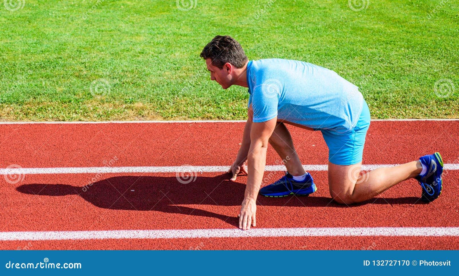 Positionsstadionsweges des Mannathletenläuferstands sonniger Tag des niedrigen Anfangs Unternehmen Sie Anstrengung für Sieg Läufe