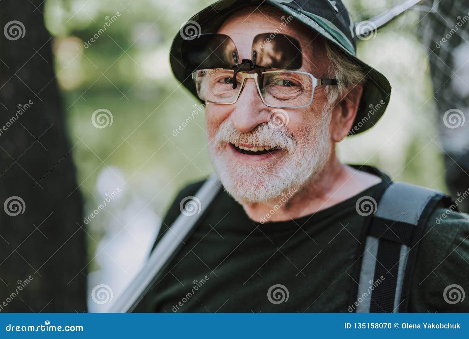 Positiv äldre man som ler på kameran