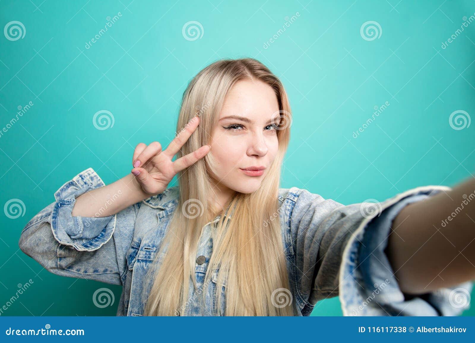Positiv blond-haired kvinna som tar selfie på blå bakgrundsdanandegyckel med henne