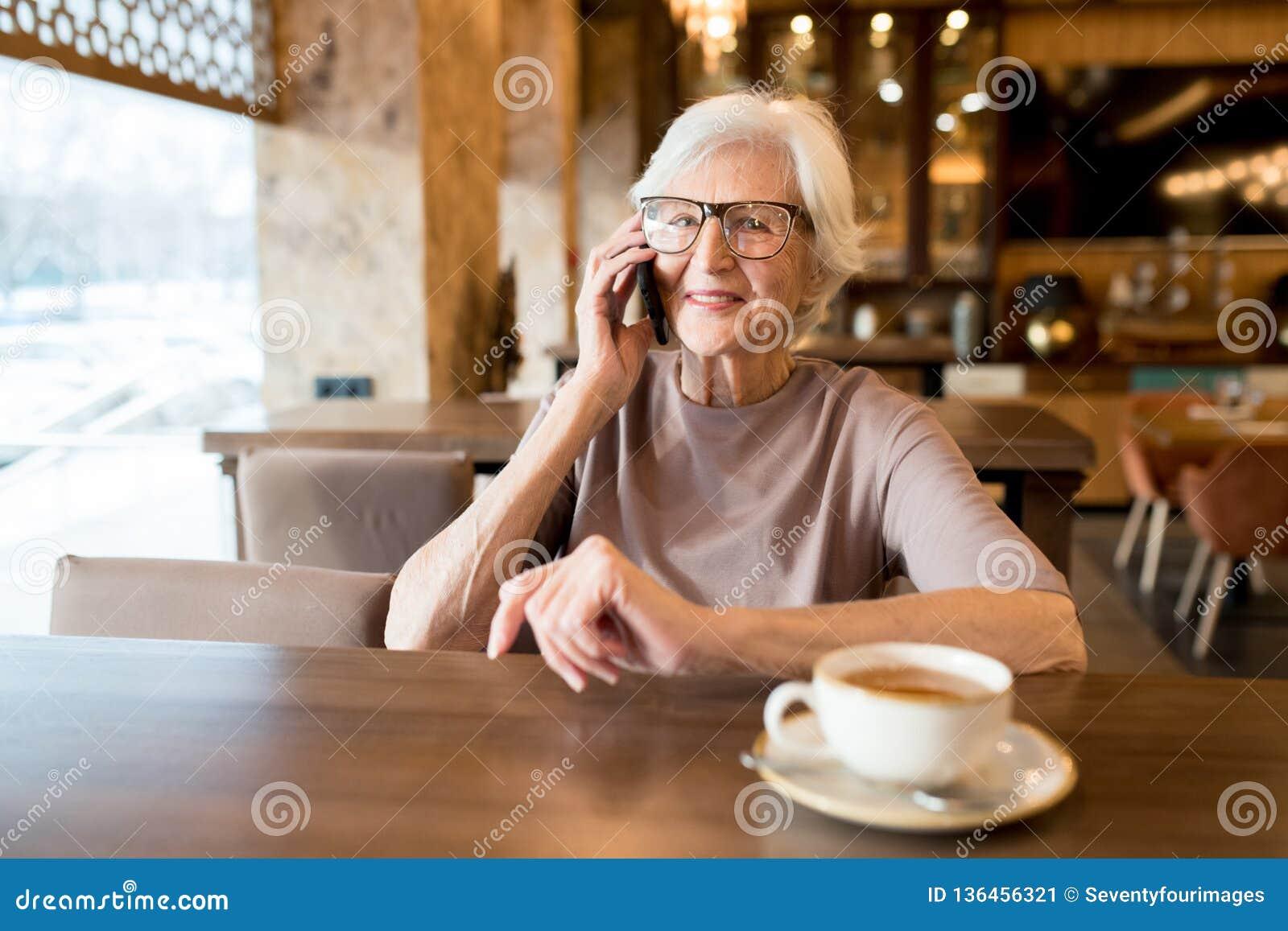 Positiv hög entreprenör som talar vid telefonen