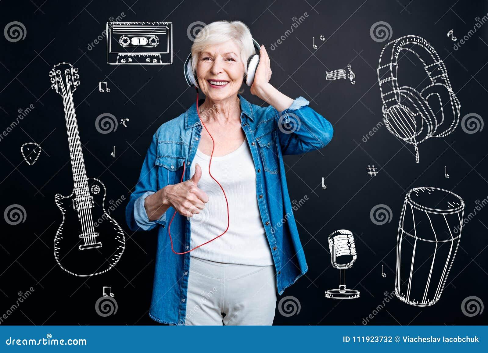 Positiv hög kvinna som sätter upp hennes tumme, medan lyssna till musik