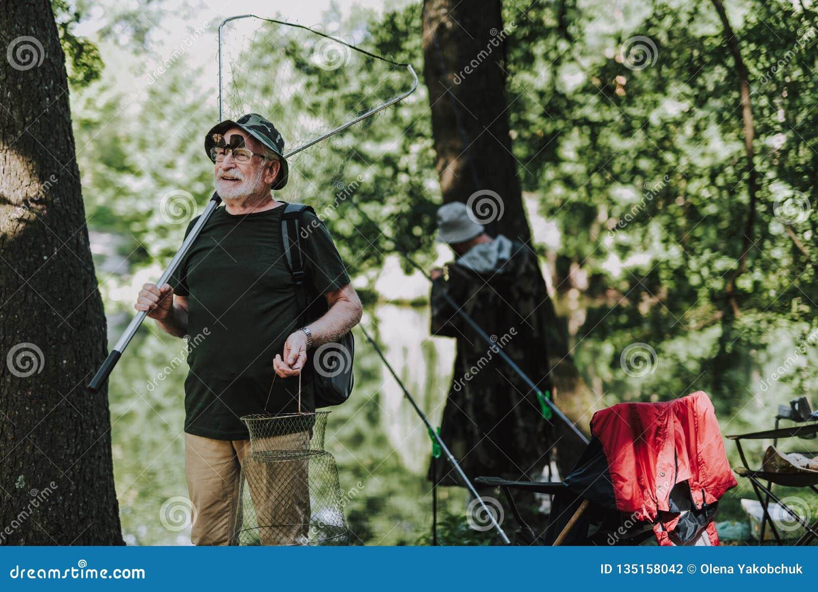 Positiv manlig fisher som rymmer yrkesmässig fiska utrustning