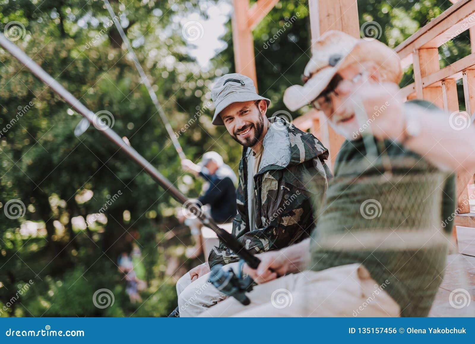 Positiv skäggig man som fiskar med hans åldriga fader