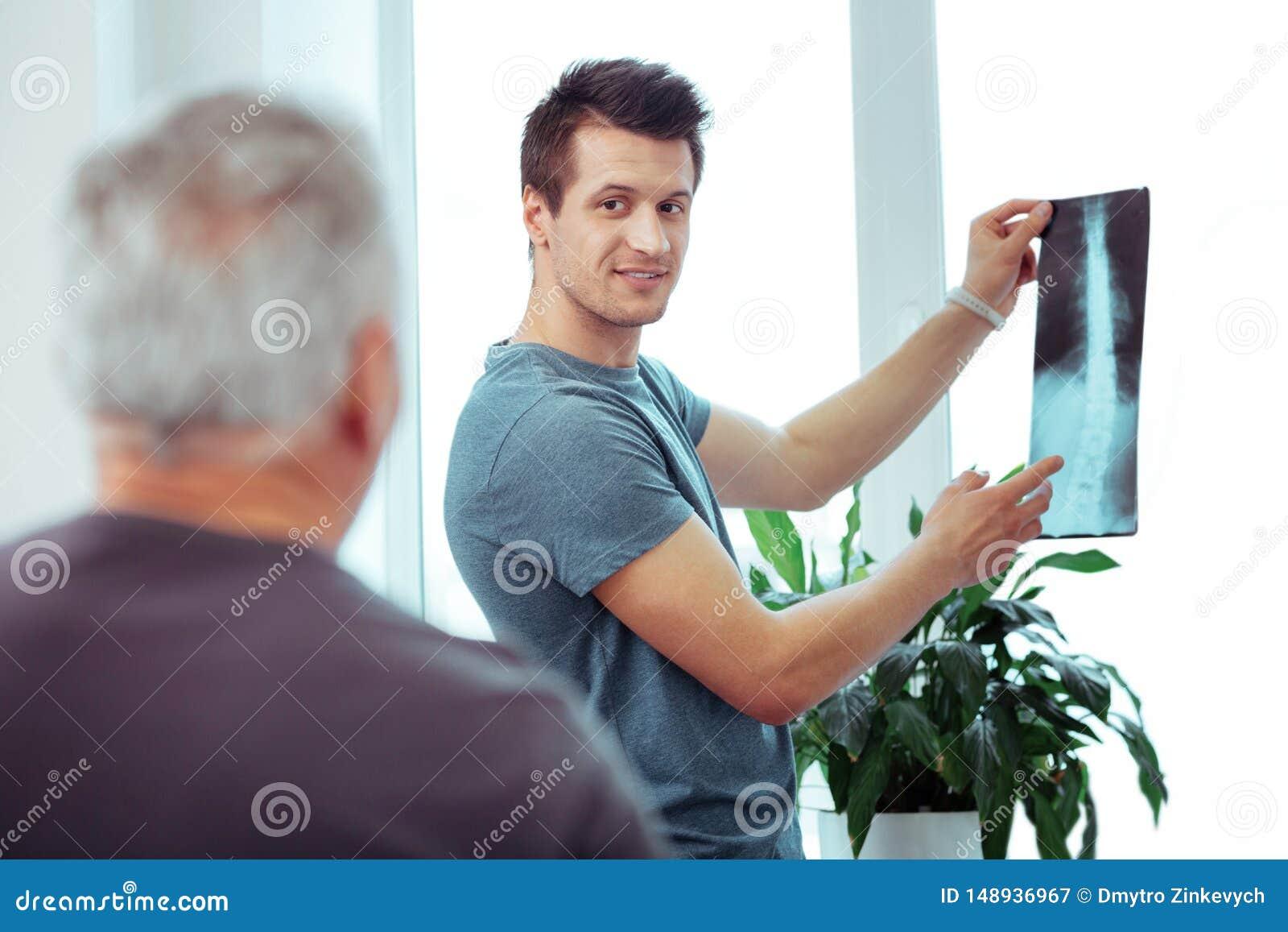 Positiv ung man som visar en bild f?r str?le X