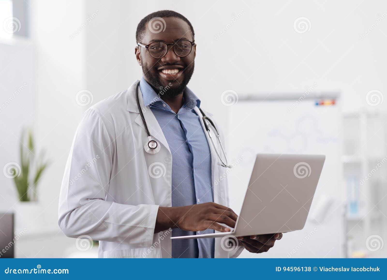 Positiv yrkesmässig doktor som arbetar på bärbara datorn