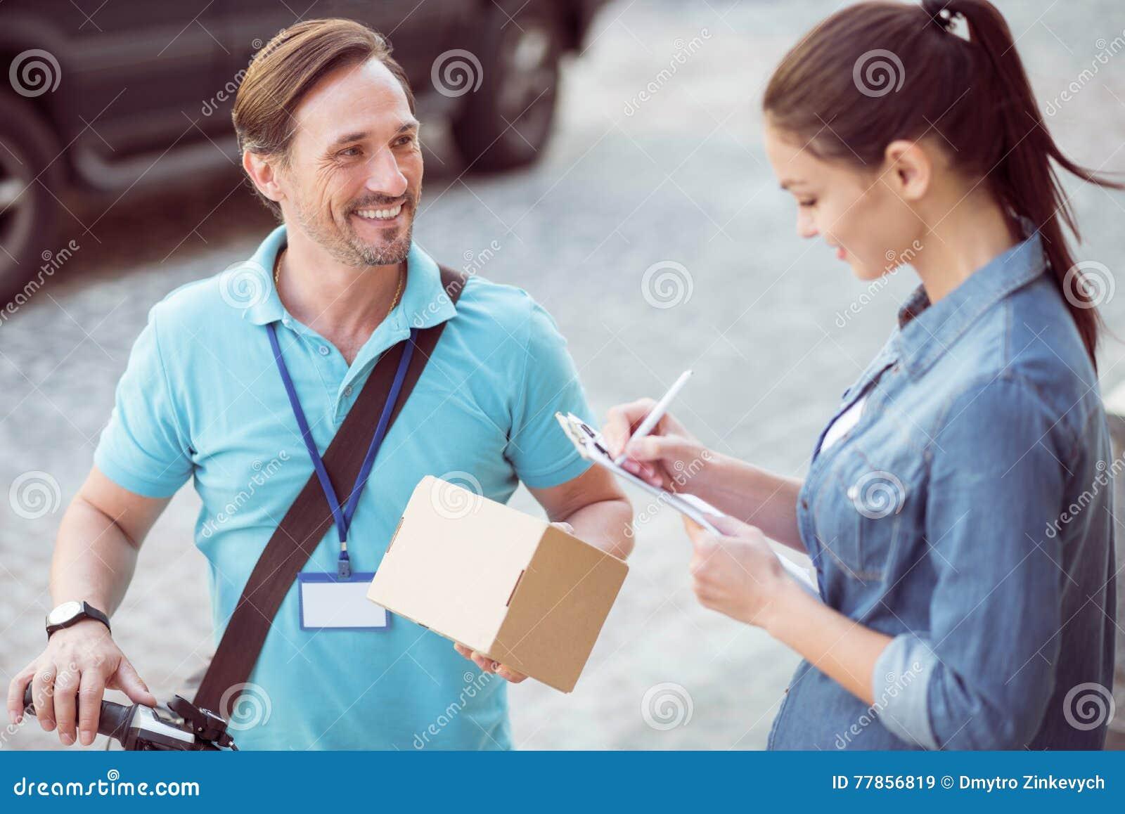 Positiv yrkesmässig kurir som levererar jordlotten