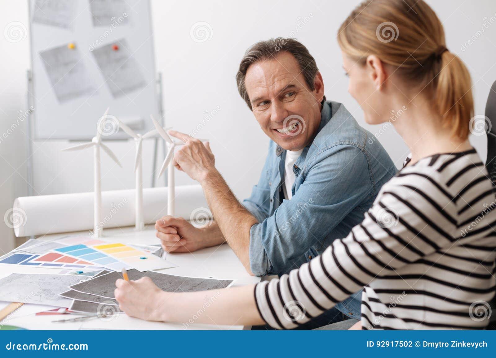 Positiv yrkesmässig tekniker som diskuterar arbetsfrågor med hans kollega