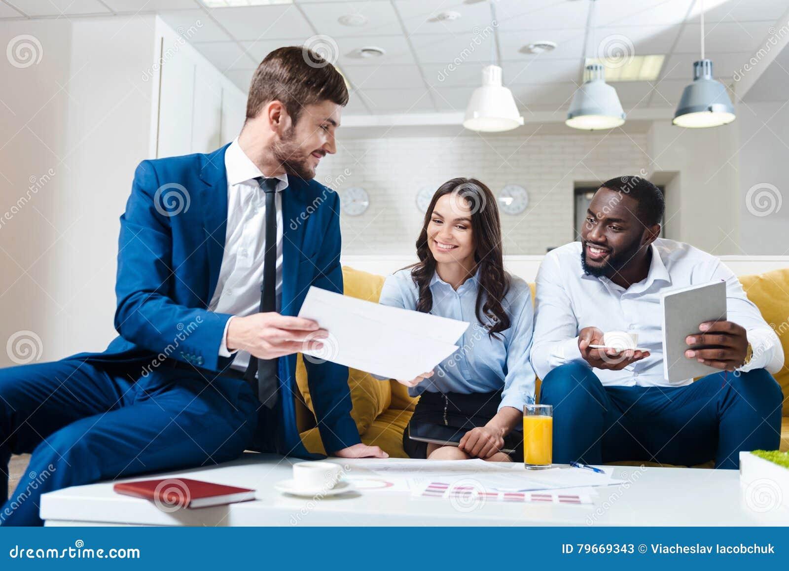 Positiva yrkesmässiga kollegor som diskuterar projekt