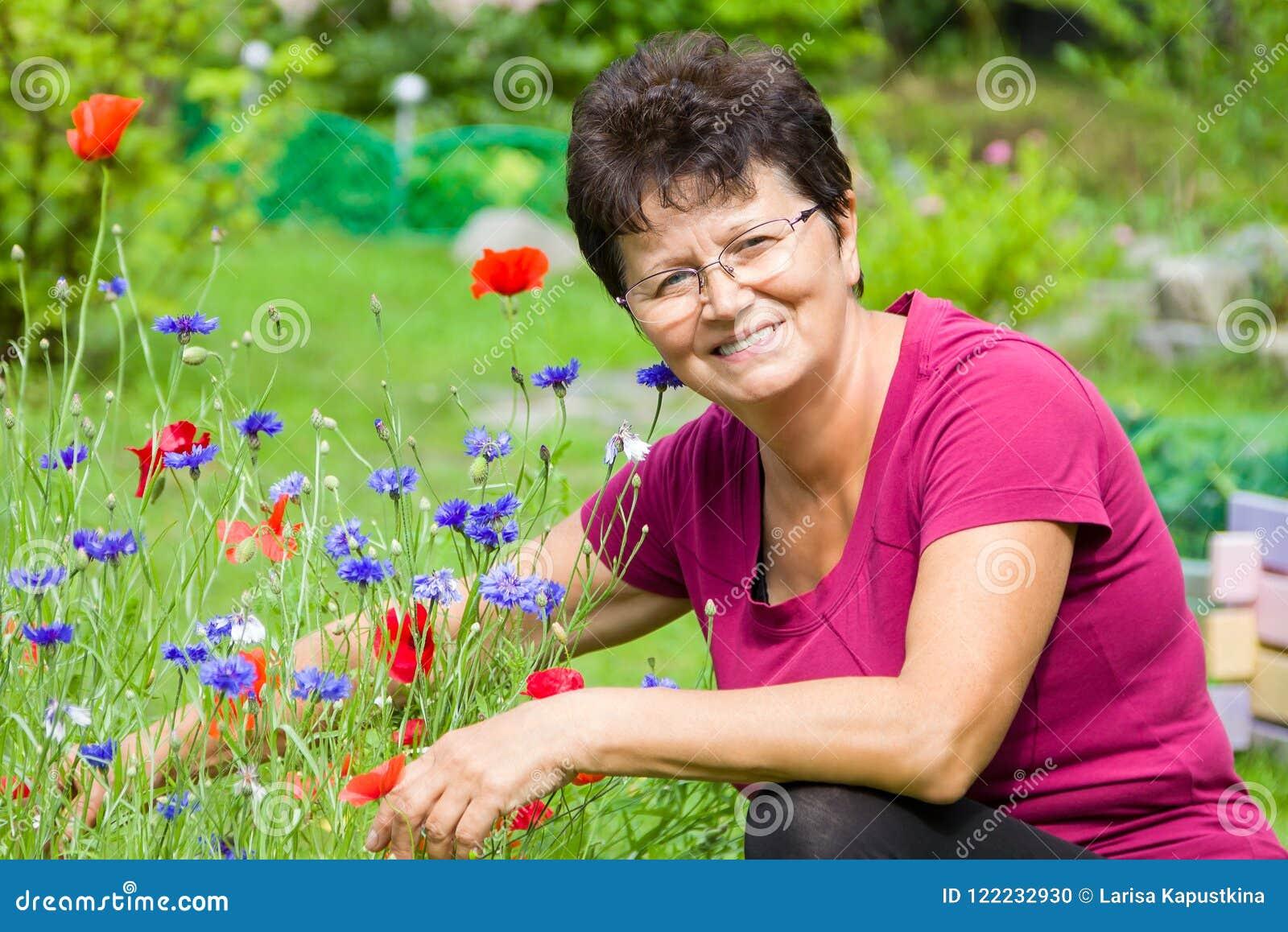 Positive ältere Frau, die unter Blumen in einem Garten sitzt