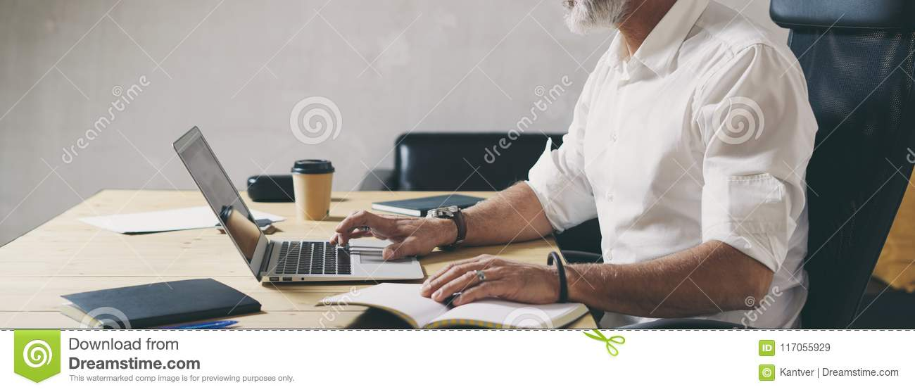 Positive bearded businessman using mobile laptop computer while sitting at wooden table at modern coworking place. Wide