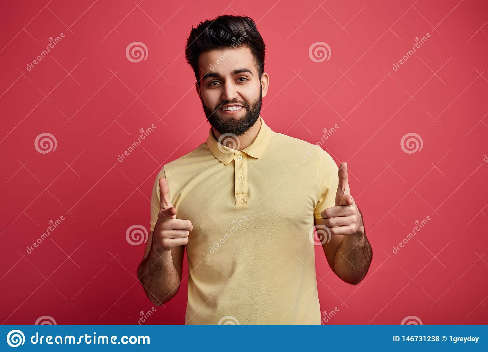 Positive bearded man in casual clothes indicates happily at the camera