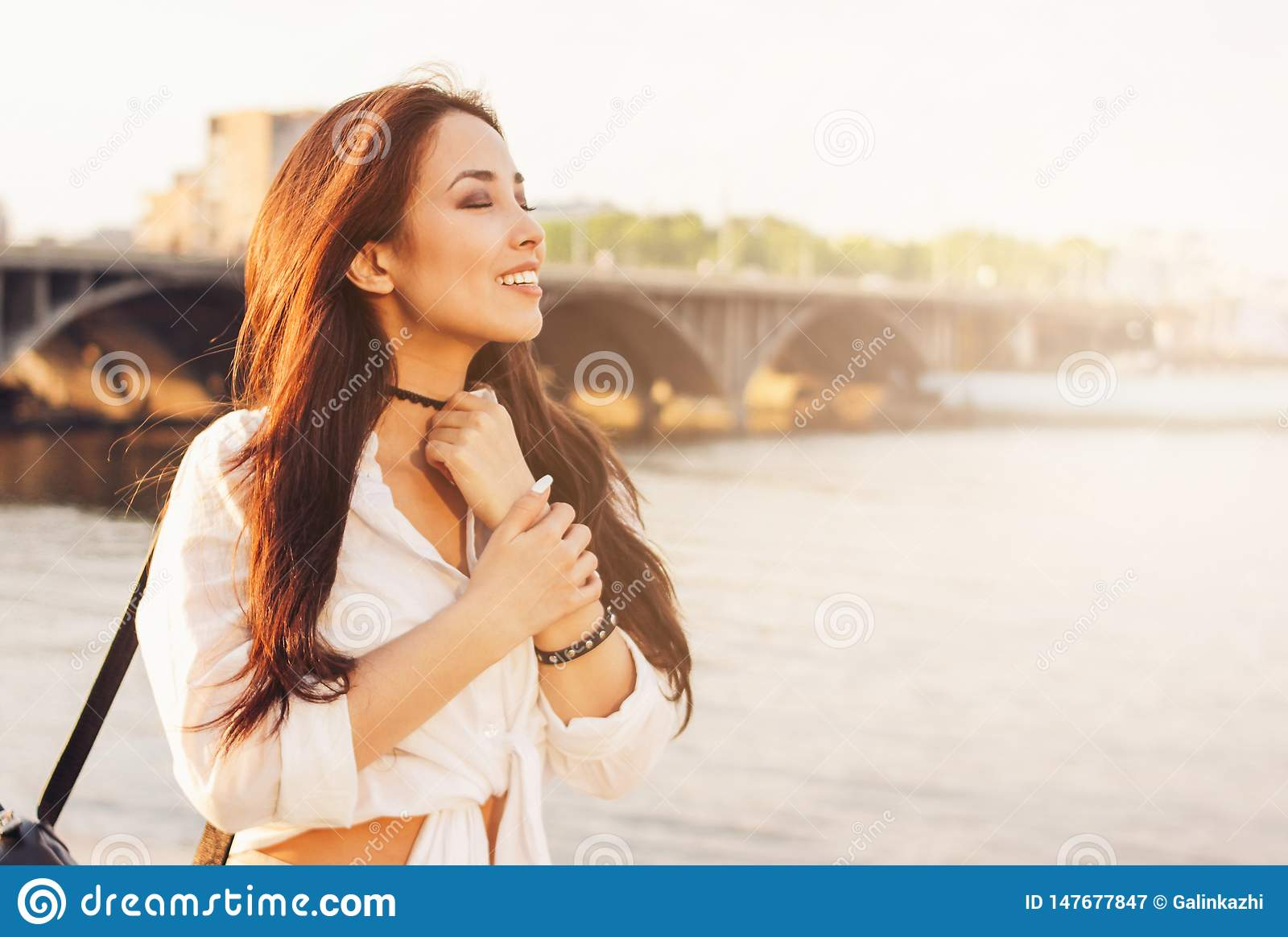 Positive beautiful long hair happy asian girl in white shirt on city river bridge background, summer travel vacation time