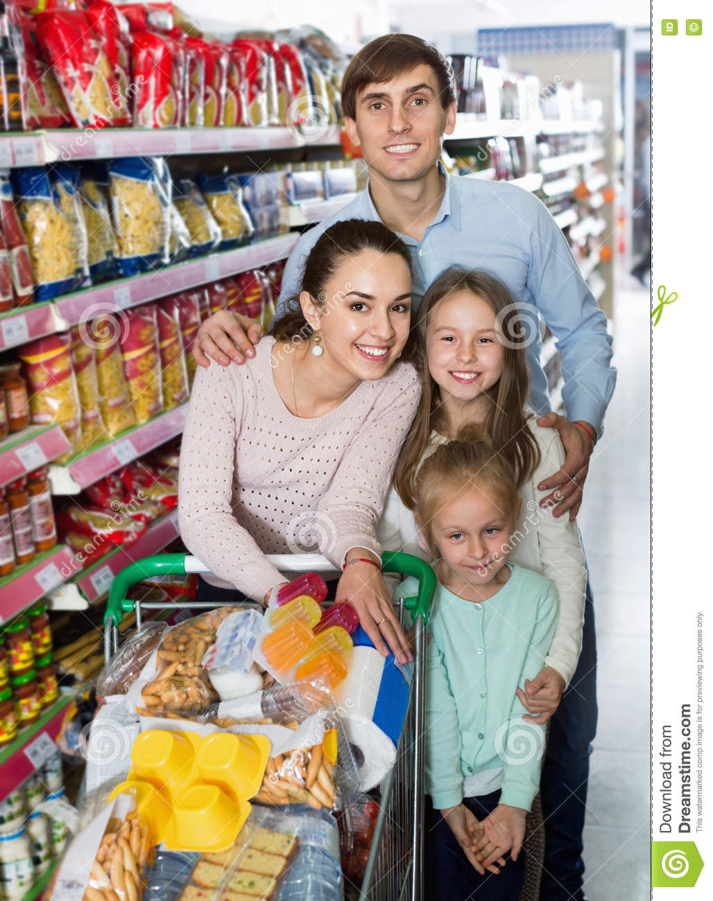 Positive customers with children buying food in hypermarket