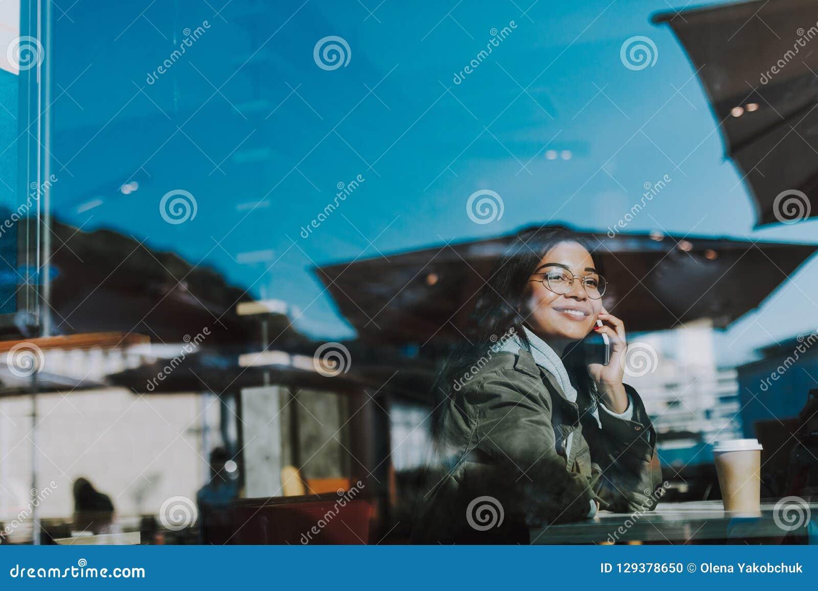 Positive Dame, die am Telefon beim Sitzen im Café spricht