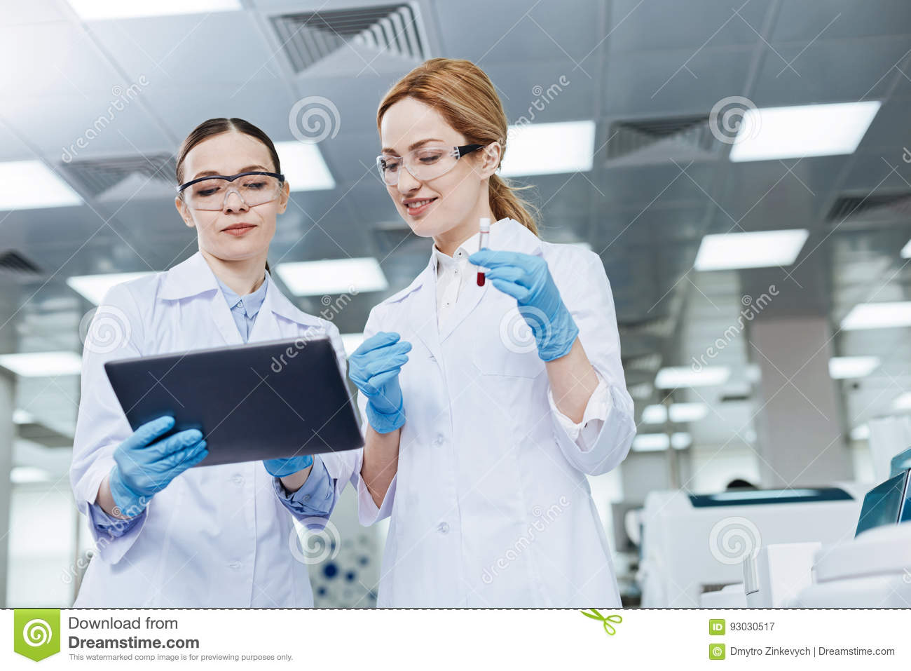 Positive delighted lab assistants looking downwards