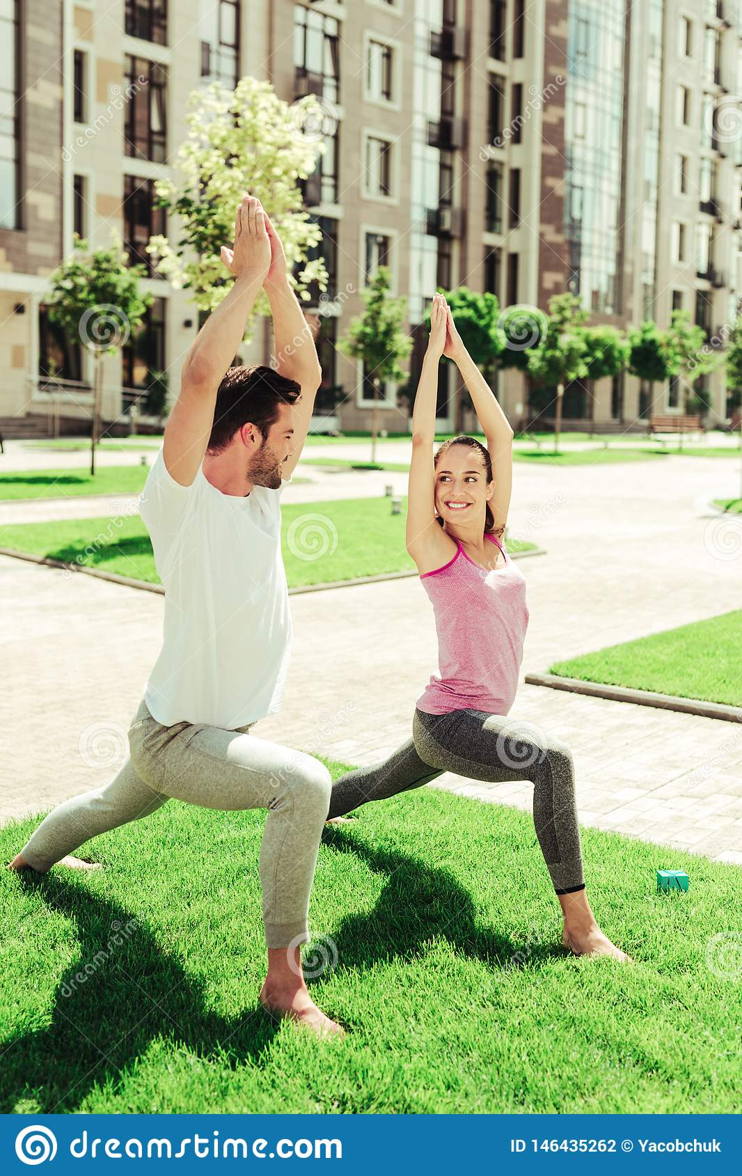 Positive delighted young people standing in asana