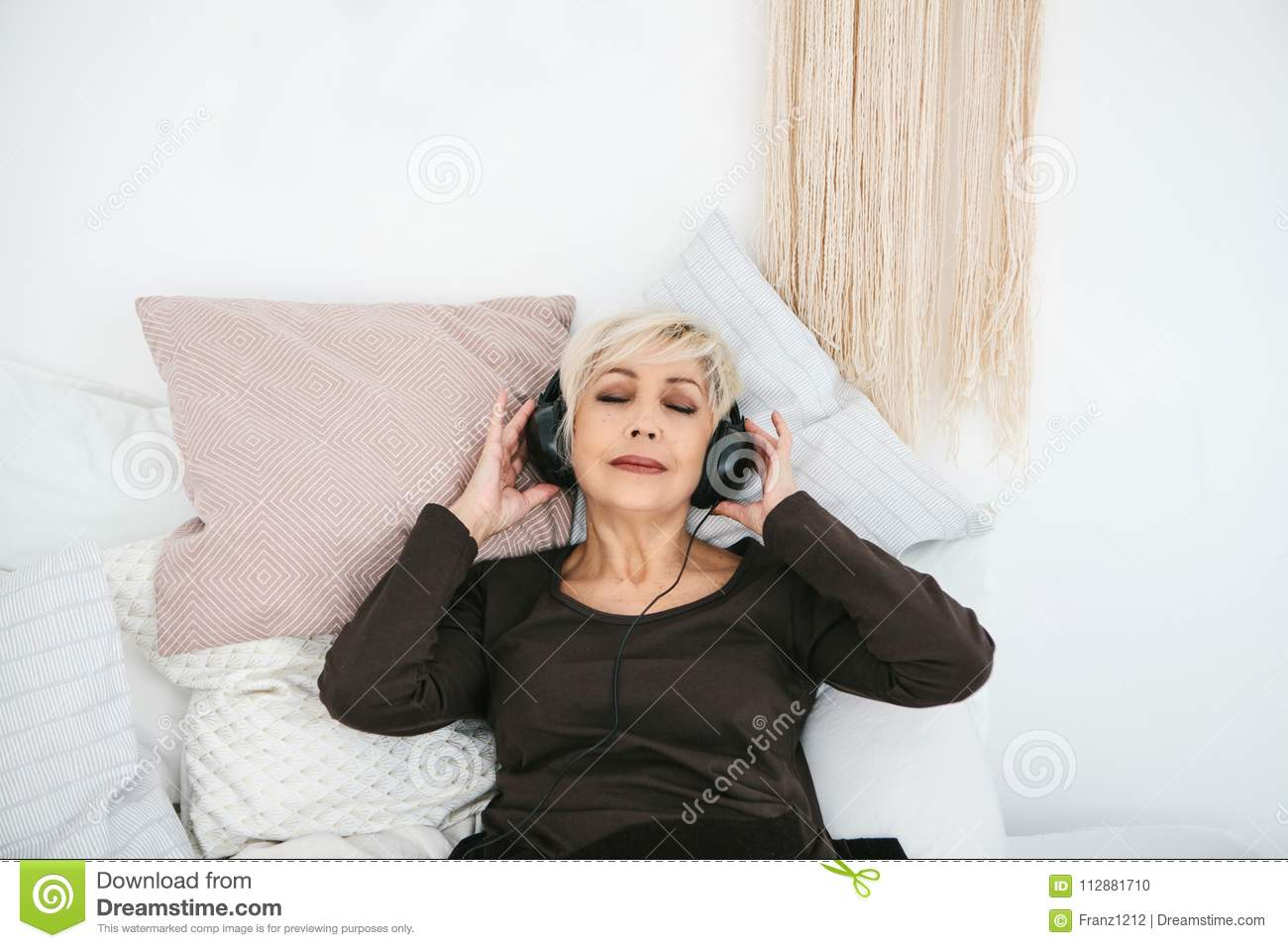 Positive elderly woman listening to music. The older generation and new technologies.