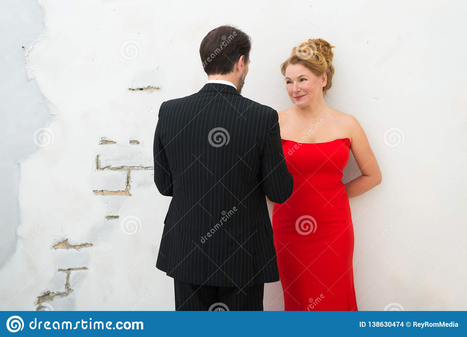 Positive elegant woman in red dress smiling sincerely while looking at her husband