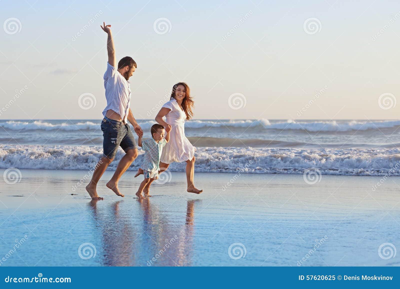 Positive family running along sea edge on the beach