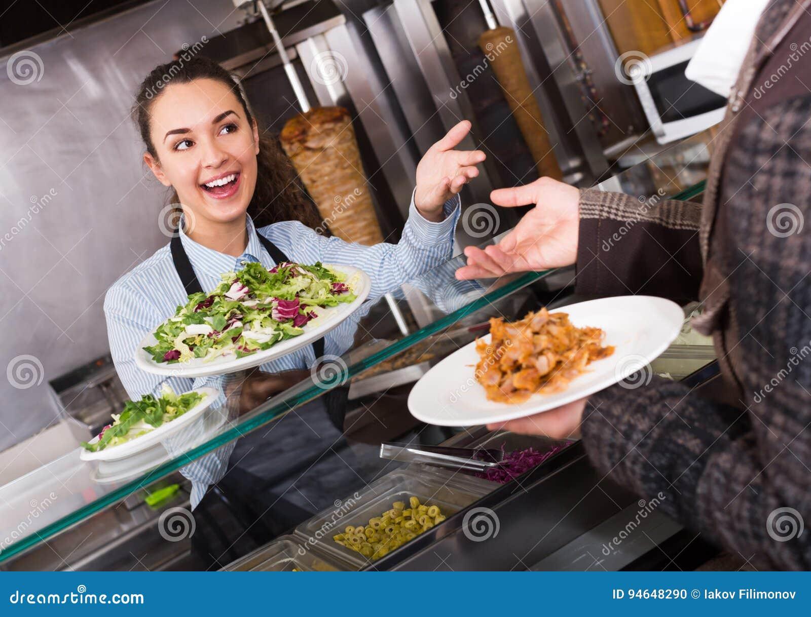 Positive female worker serving customer