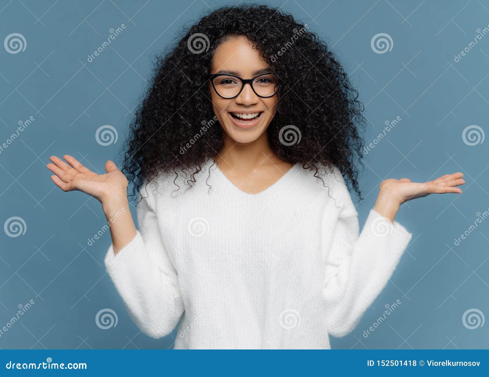 Positive freundliche junge Frau mit Afroauftritt, verbreitet Palmen, hält unsichtbaren Gegenstand, hat reizend Lächeln, gesunde H