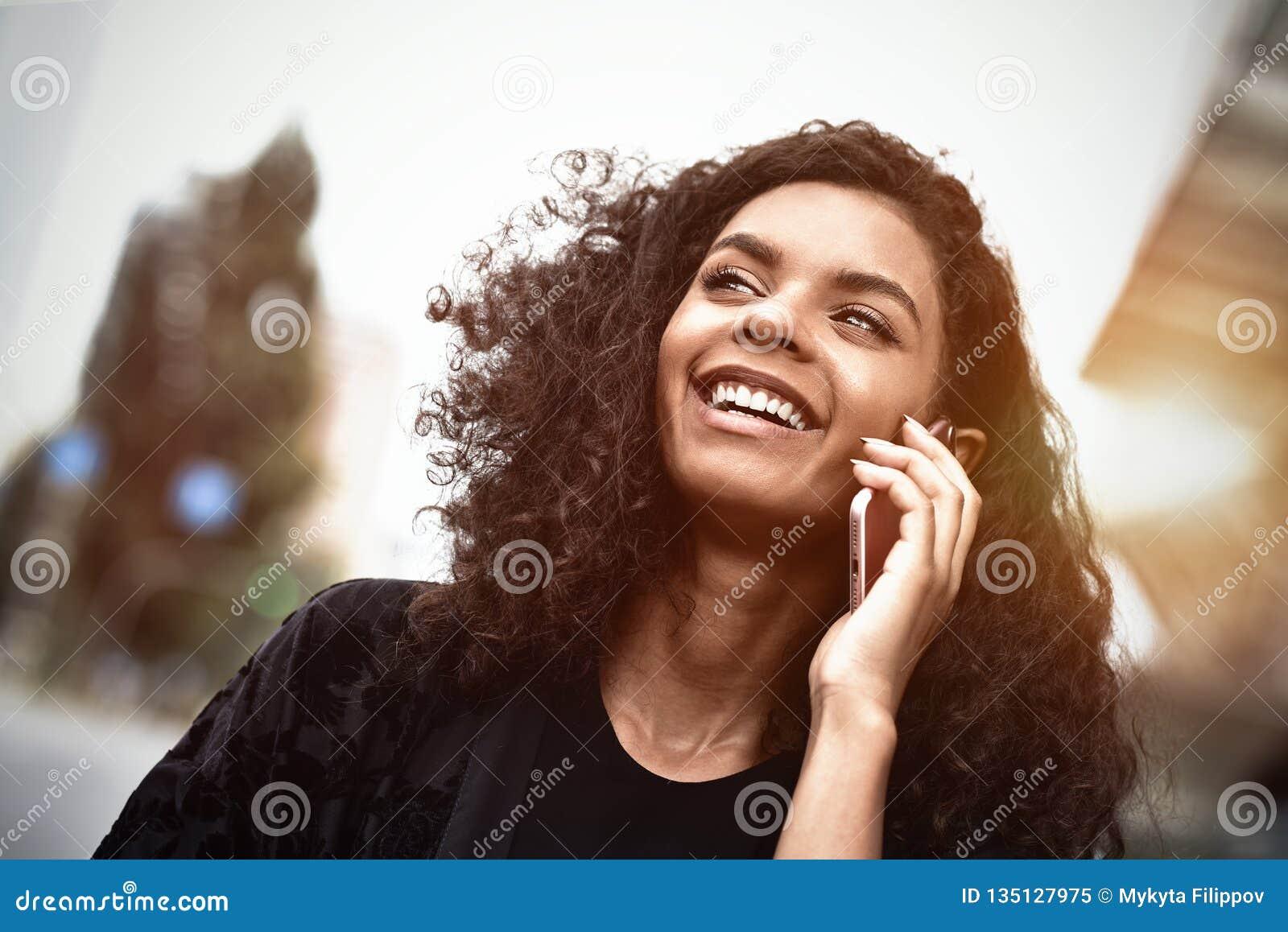 Positive Gefühle Enthalten Sie Steigungs- und Ausschnittsmaske Abschluss oben des jungen Mischrassefrauengebrauches ein Telefon