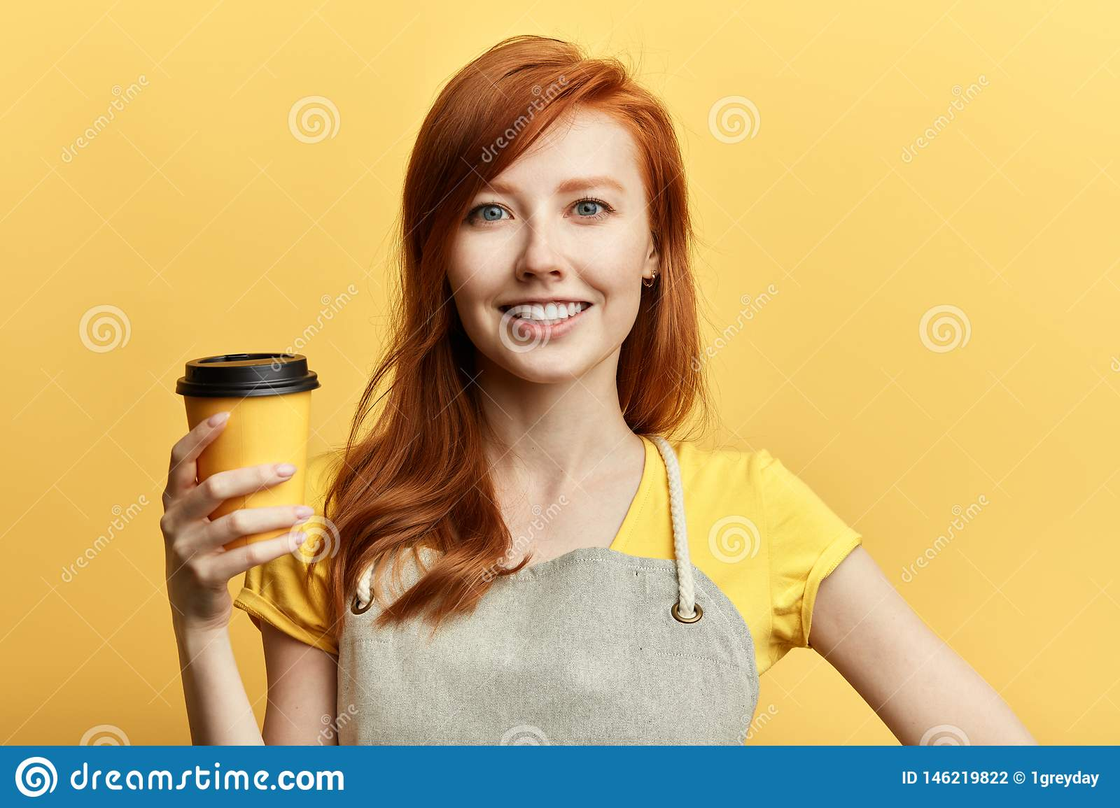 Positive gorgeous girl offering a cup of coffee