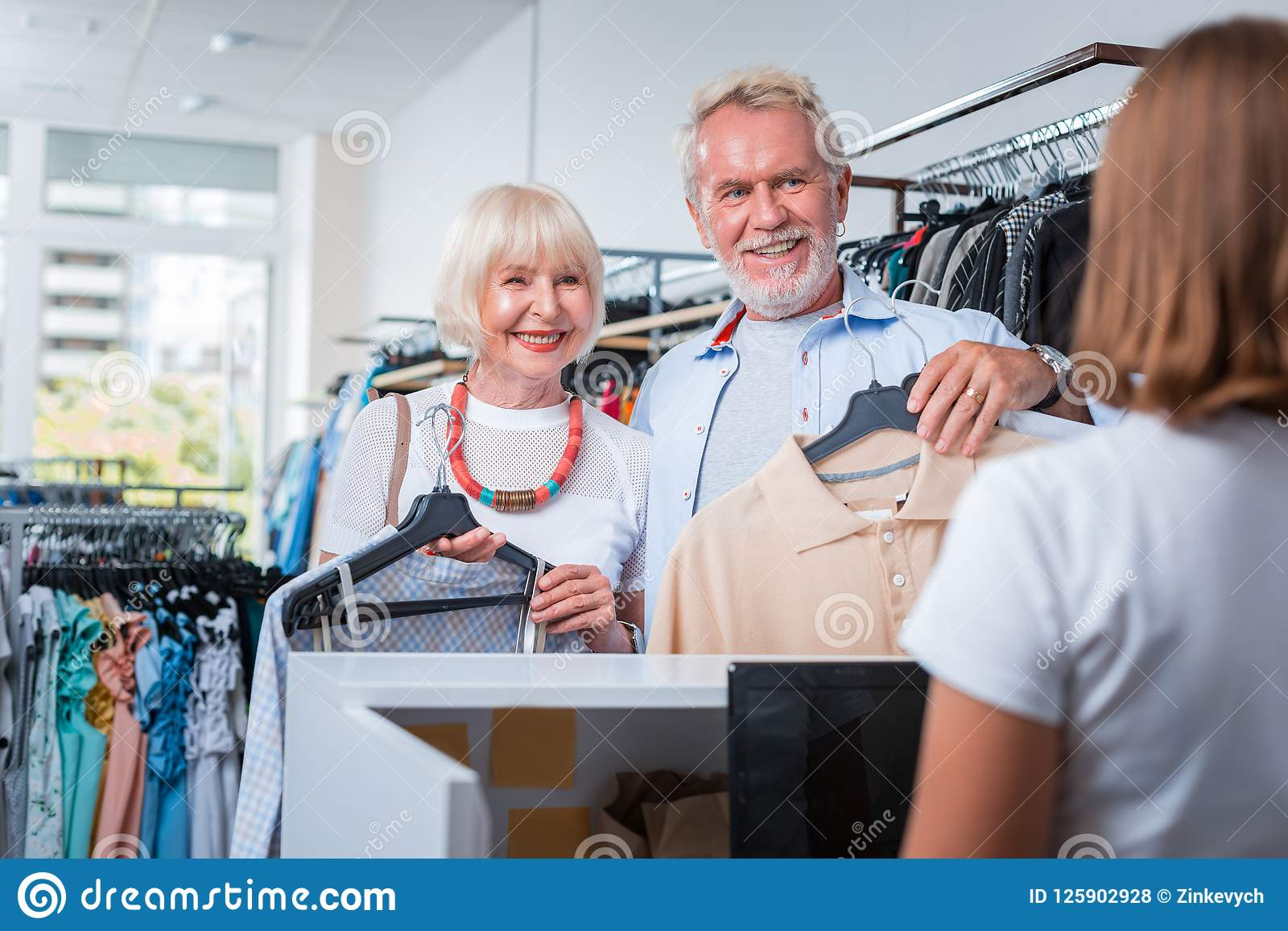 Positive grey haired customers being ready for payment process