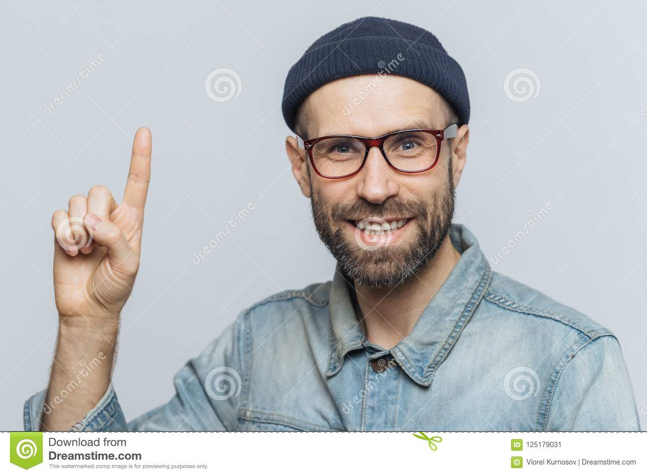 Positive handsome bearded male raises fore fimger, looks with cheerful expression directly intto camera, wears fashionable hat, sh
