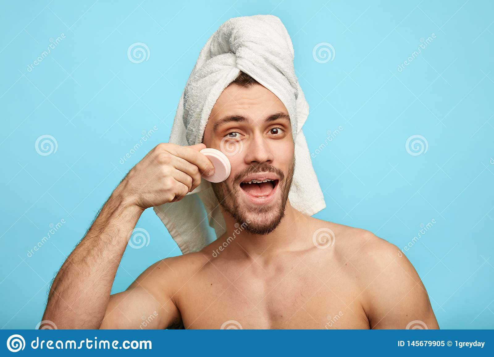 Positive happy man applying powder on his face