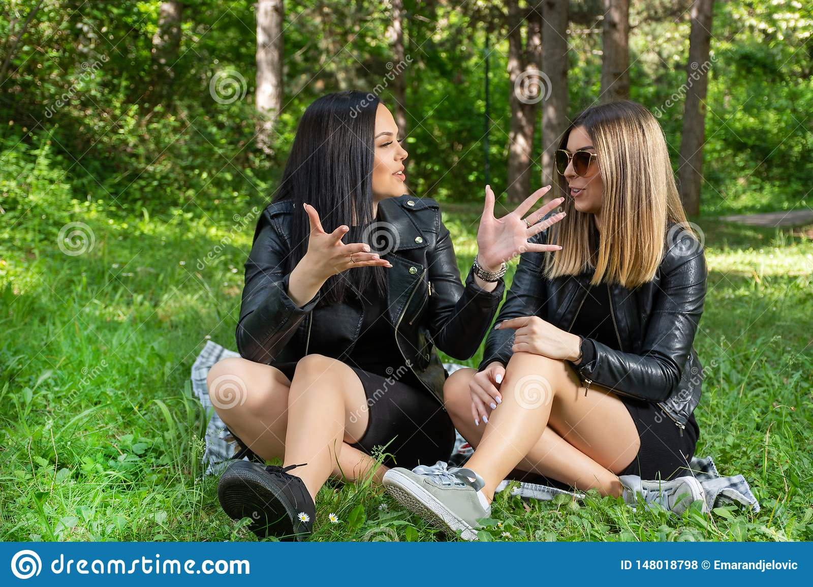 Positive and happy girls talking in nature and sitting in the meadow on a blanket, girls laugh and enjoy on a beautiful spring day
