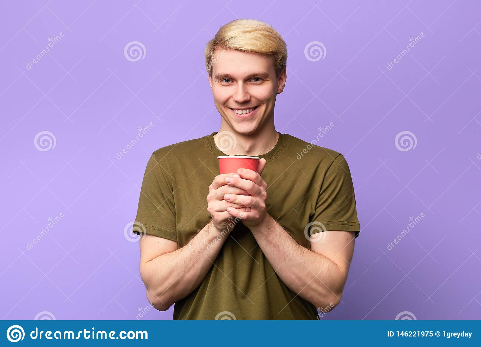 Positive happy young handsome man looking at camera and holding plastic cup.