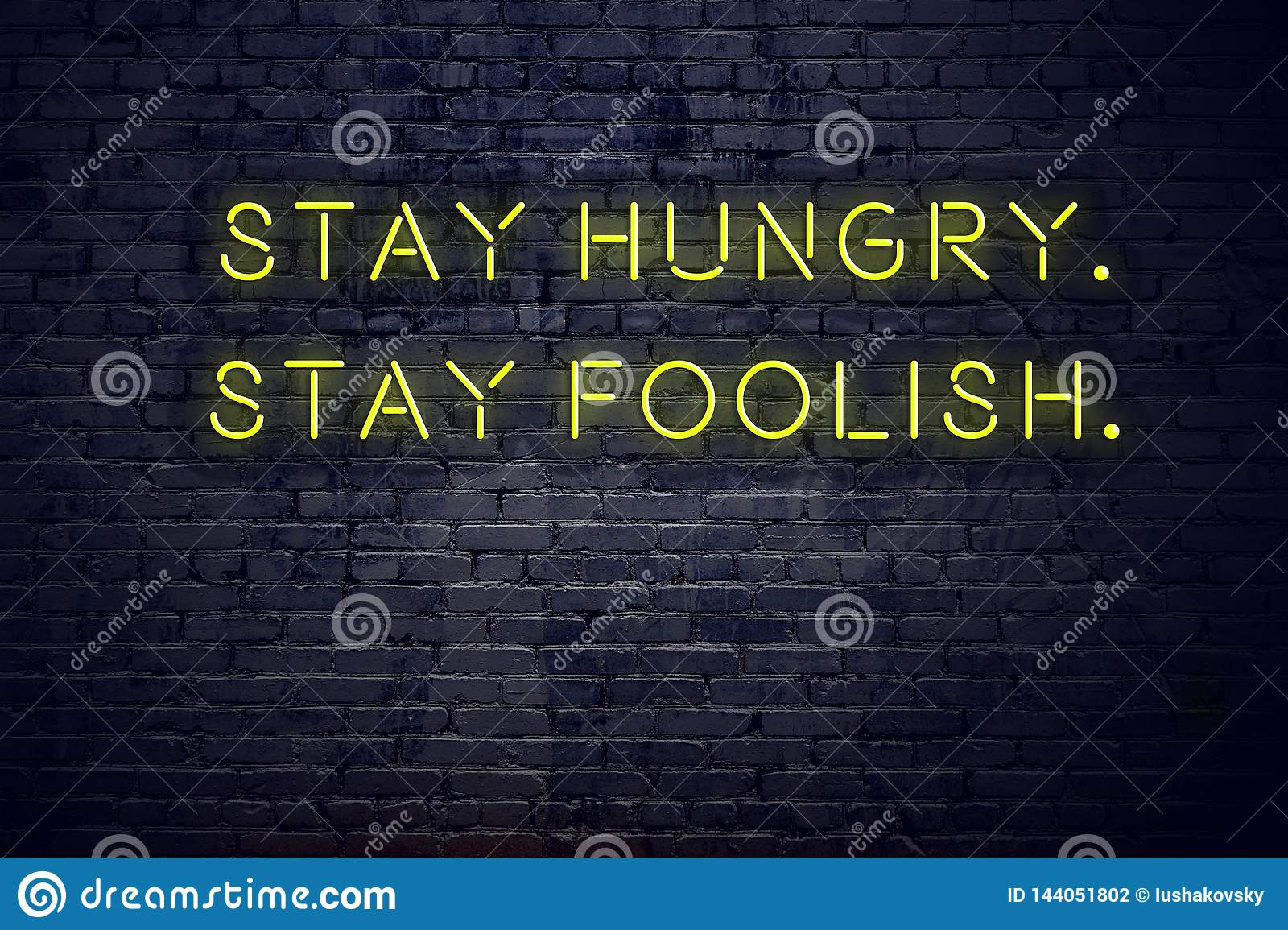 Positive inspiring quote on neon sign against brick wall stay hungry stay foolish