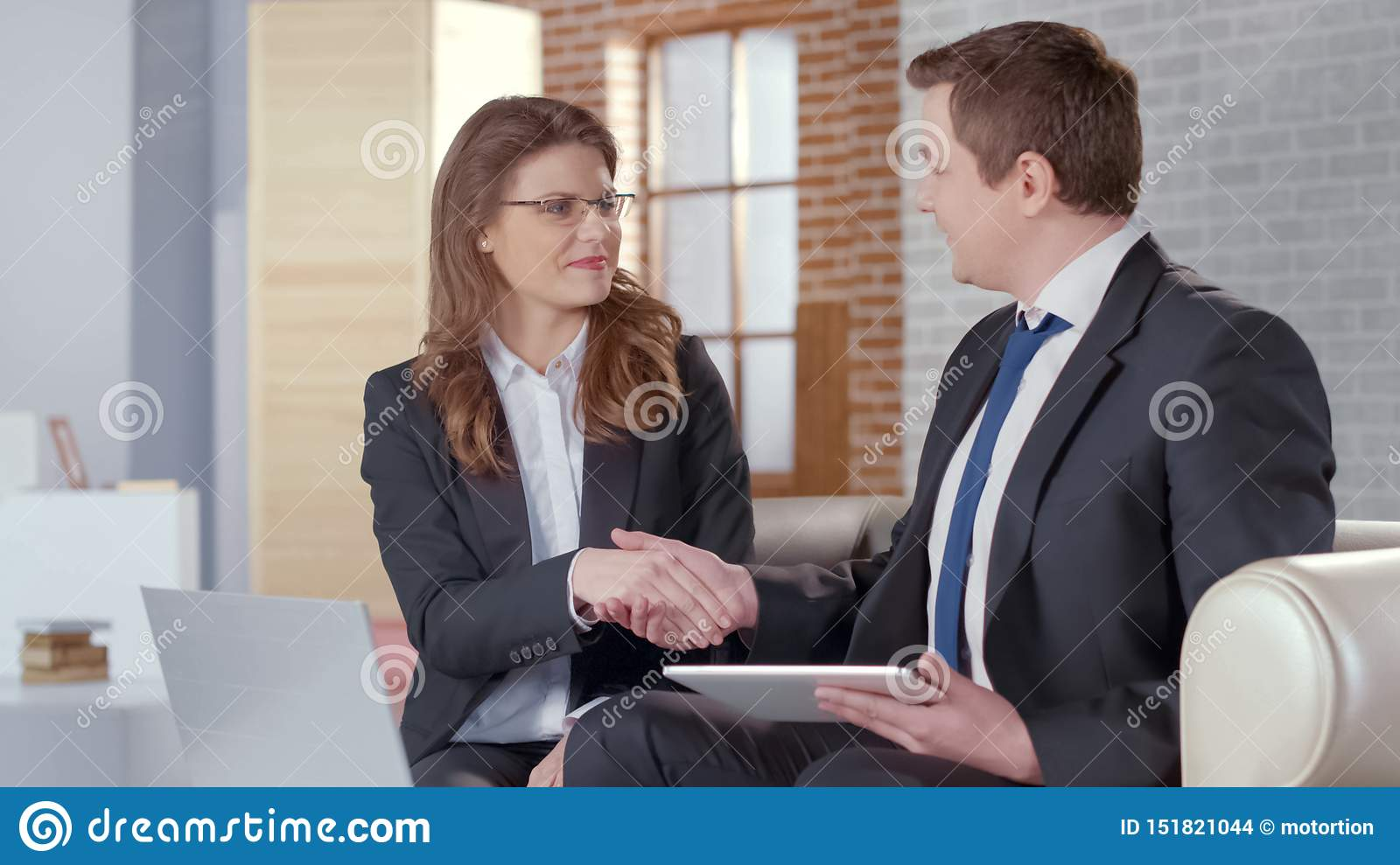 Positive male and female business partners shaking hands, successful agreement
