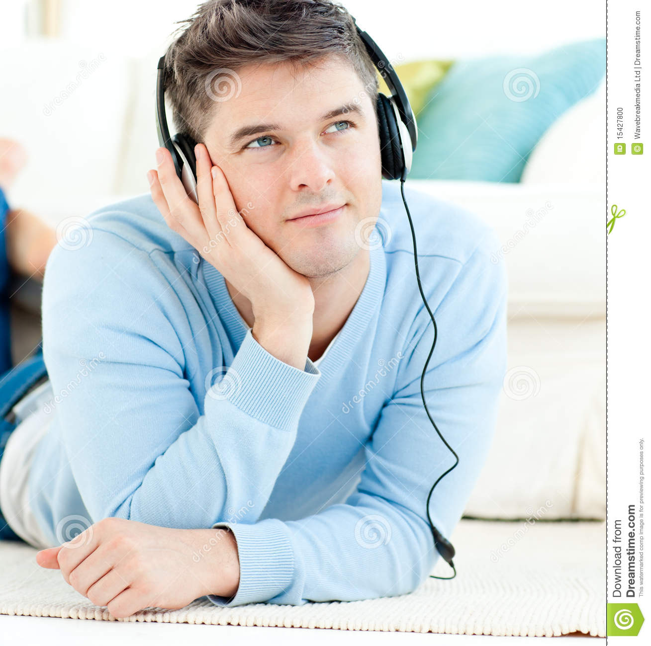 Positive man with headphones lying on the floor in the living room