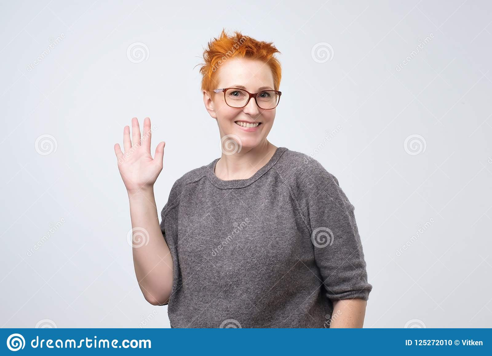6800c5ca3ec1 Positive mature caucasian woman with red hairstyle and glasses smiling  friendly and waving hand at camera.