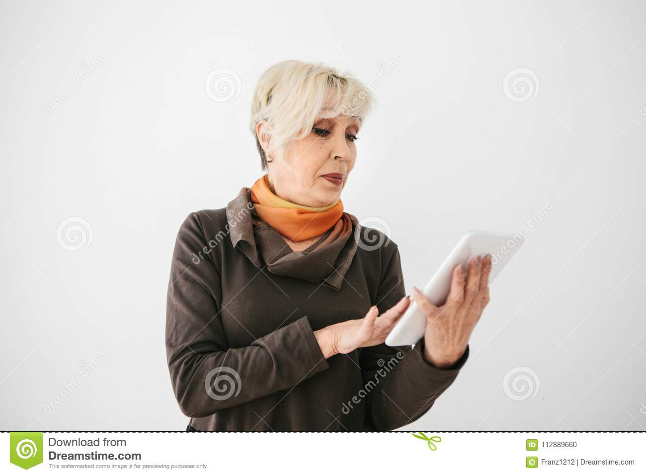 A positive modern elderly woman holds a tablet in her hands and uses it. The older generation and modern technology.