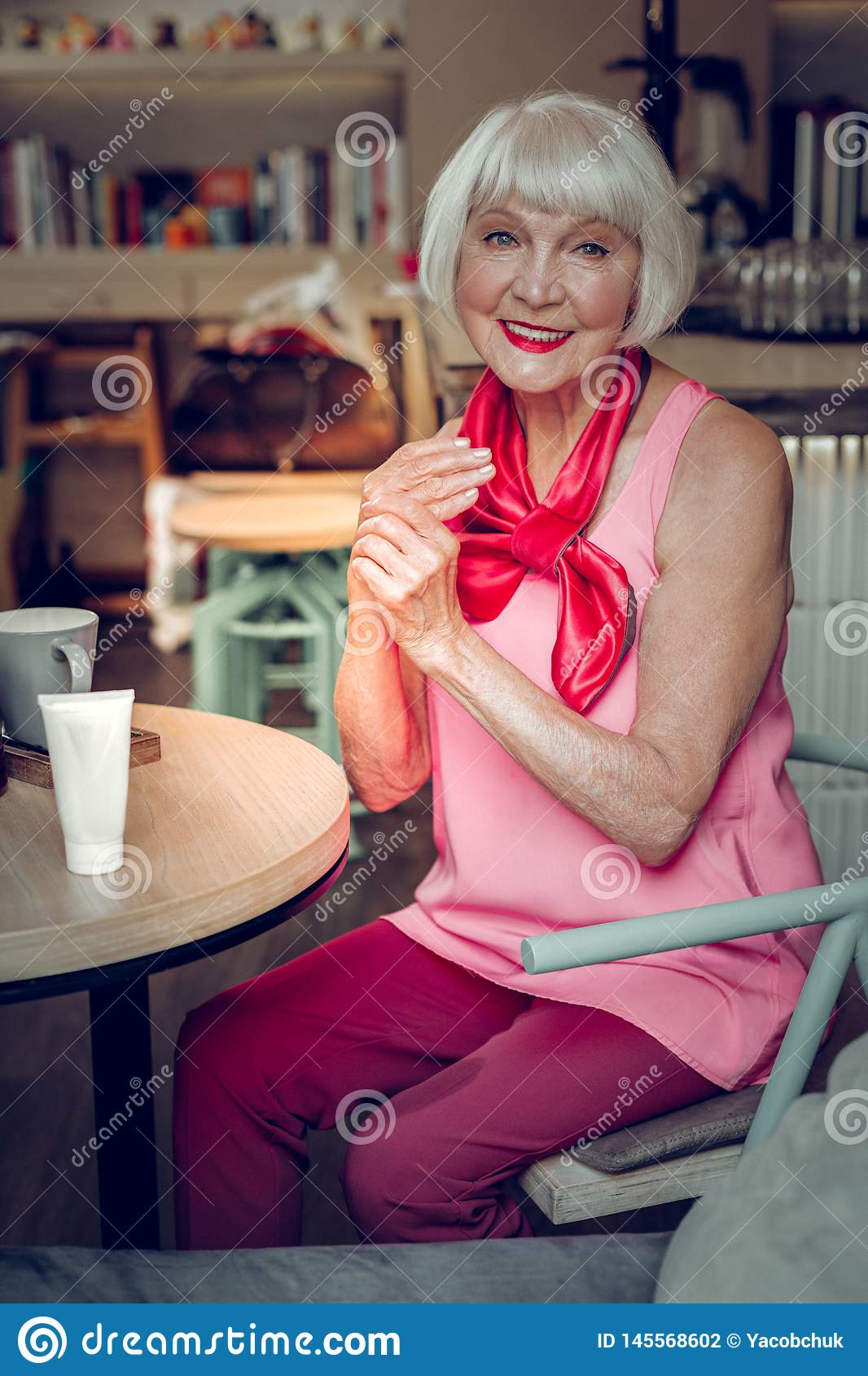 Positive cheerful woman sitting at the table