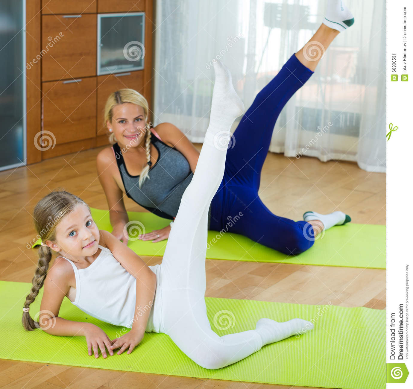 Positive Mother And Little Daughter Working Out At Home ...