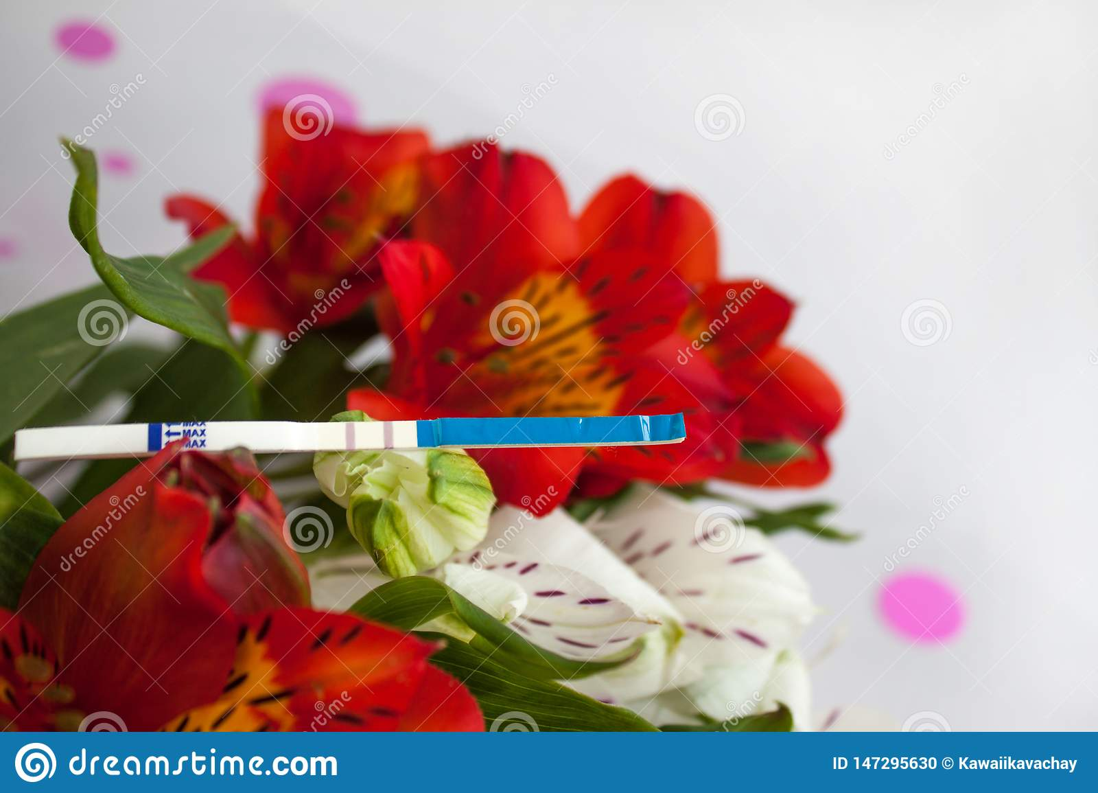 Positive pregnancy test with a bouquet of alstroemeria flowers