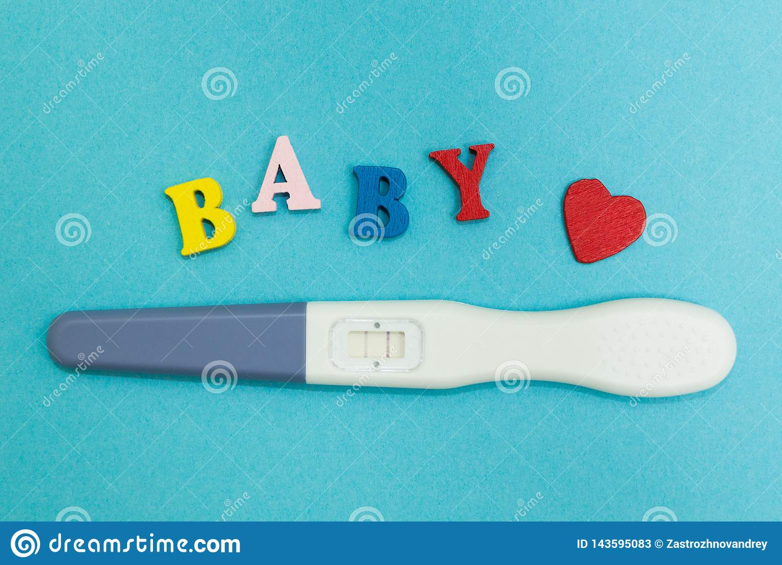 Positive pregnancy test with two strips and the word `baby` on a blue background