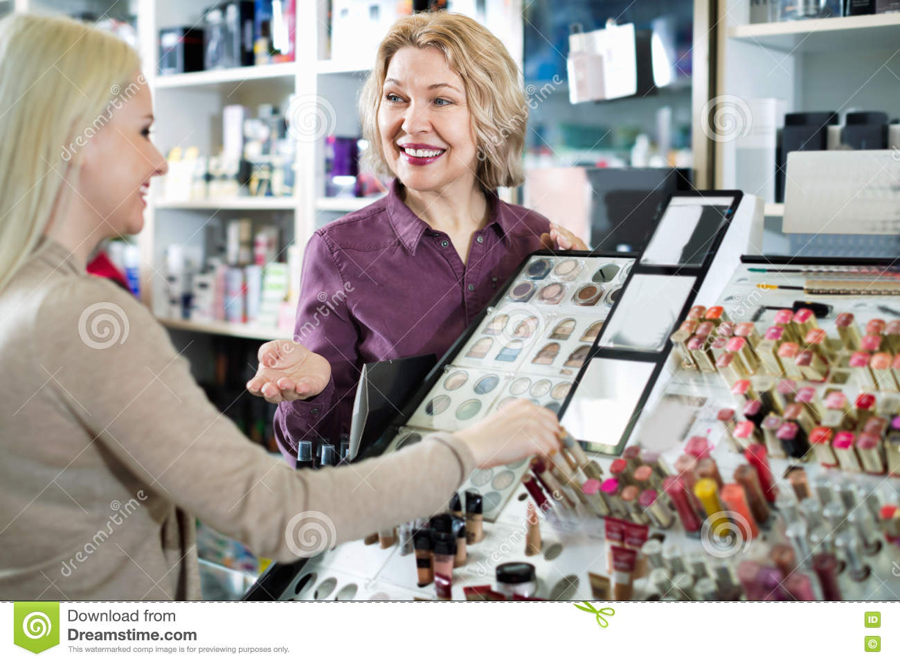 Positive seller helps customers choose cosmetics in store