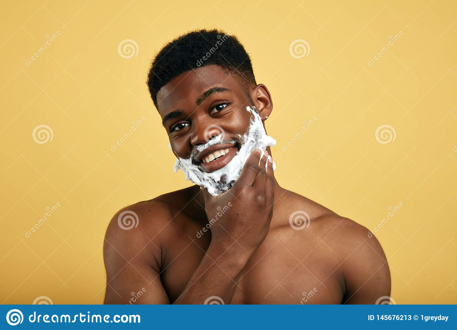 Positive shirtless man with shaving foam having a shower, touching his chin